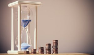 時間とお金の関係のイメージ画像。砂時計とコイン。